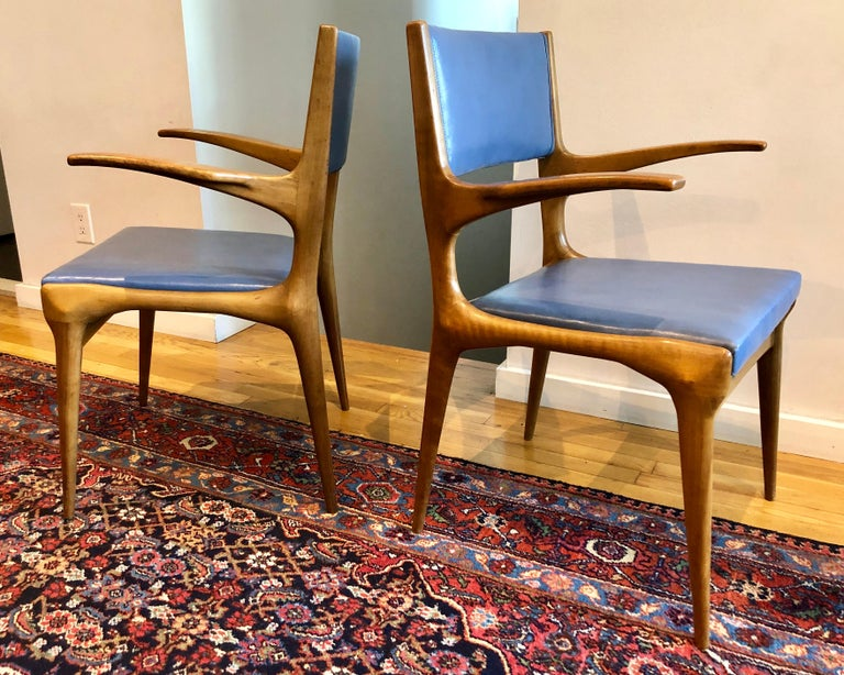 Italian walnut armchair with original blue skai upholstery, beautifully carved with an animal-like fluidity. By Cassina, retailed through M. Singer and Sons.