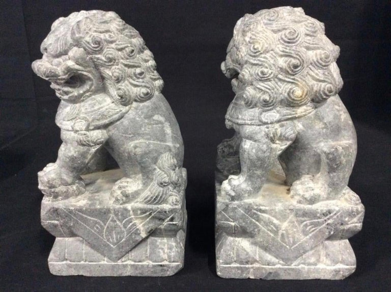 Pair of foo or Fu dogs carved from jade stone. Also known as Chinese foo dogs, Chinese temple dogs, temple lions stone sculpture.