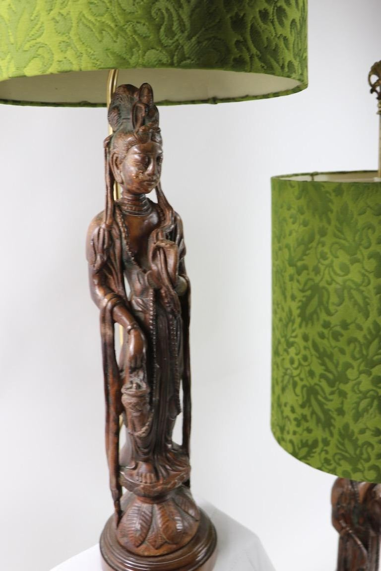 Very stylish and chic pair of carved wood Tibetan Buddha table lamps, complete with original decorative shades. 55 in Total H x 29 in H of Buddha figure x Shade 21 in H x 17 in Dia. x 7 in. Dia. of Base. Offered and priced as a pair.