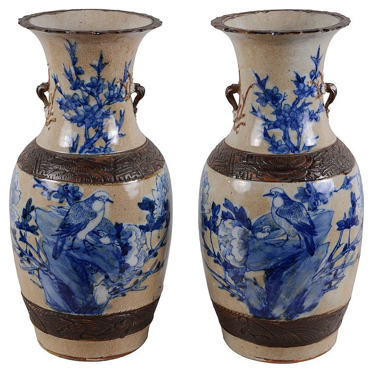 Pair of 19th century Chinese blue and white crackleware vases, each with brown colored engraved bands, and blue and white scenes of Doves on a rocky outcrop surround by flowers and leaves. We can have these vases wired as lamps if required within
