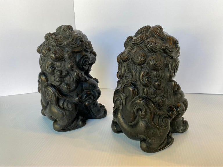 Pair of Chinese lions completely hand carved out of solid bamboo root. They would make excellent decorative book ends or guardian door stops. Sweet faces with a smile and curly hair depicted