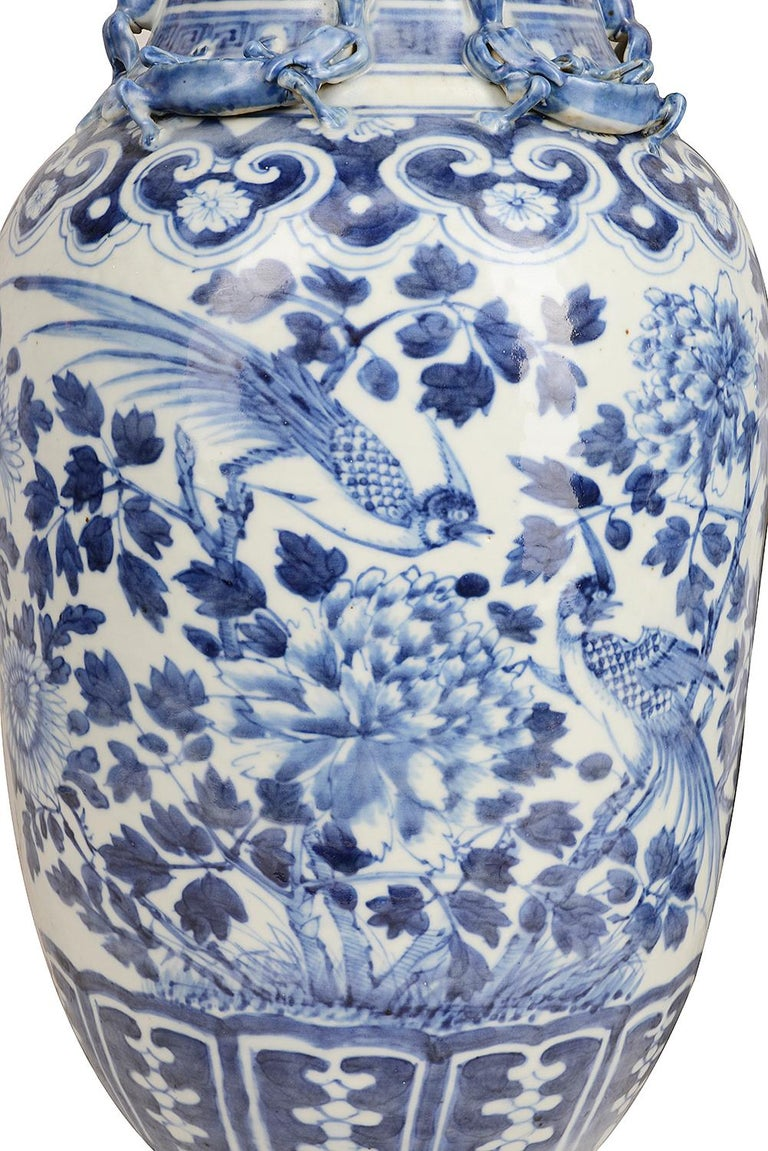 A good quality pair of 19th century Chinese blue and white vases, each with exotic birds amongst leaves and flowers, lizard mounts to the neck and classical motifs to the neck and base.