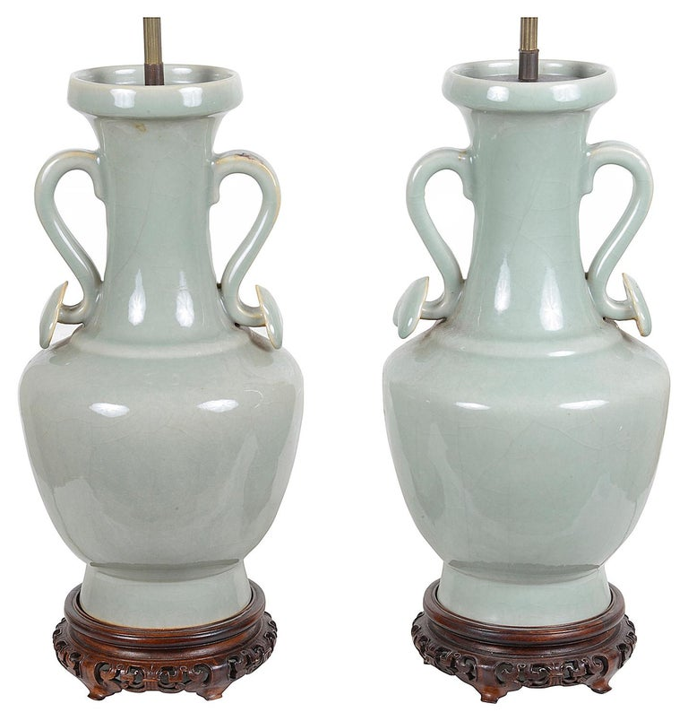 A very decorative pair of 18th century style Chinese Celadon porcelain two handled vases / lamps, raised on carved pierced hardwood stands, circa 1920.