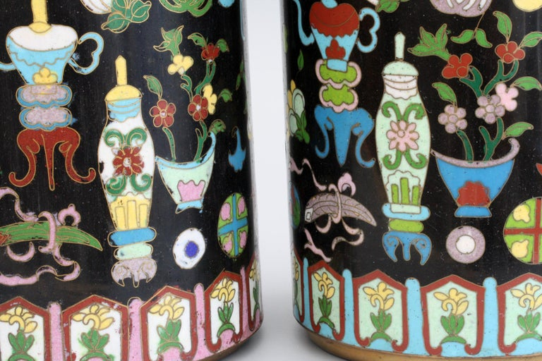 An exceptional and stunning pair cylindrical Chinese cloisonné enamel sleeve vases dating from the early 20th century, probably late Qing. The tall pair of vases are brightly decorated in colored enamels on black grounds decorated with scholars and