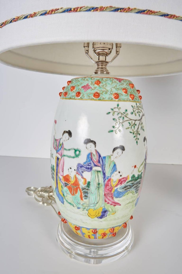 Pair of vintage Chinese porcelain drum shaped decorative porcelains now custom mounted as lamps with custom shades. Porcelains rest on custom Lucite bases. Custom shades are in white silk trimmed with blue, celadon, coral and metallic gold colored