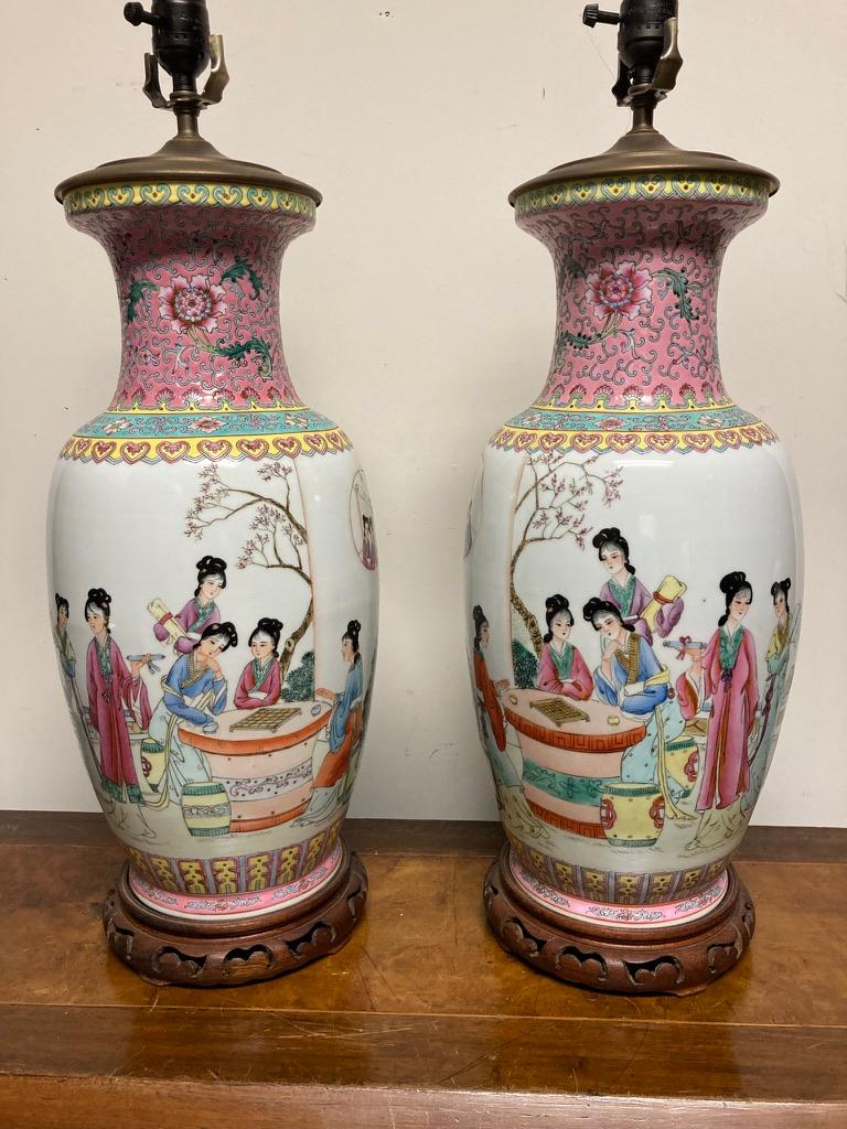 Nice pair of famille rose lamps, finely enameled with court ladies playing mahjong at a table in a garden setting as others look on. Four lines of calligraphy, with seal marks. The neck decorated with stylised flowers and scrolls on a pink ground,