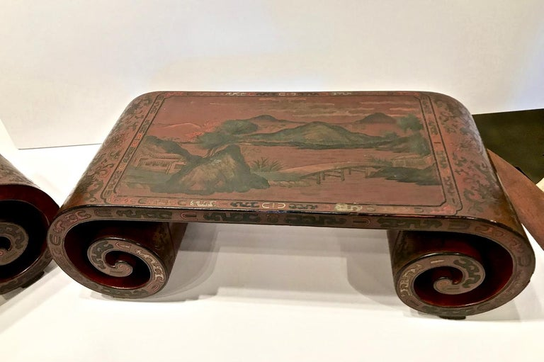 This is a very unusual pair of Chinese sang de boeuf lacquered scroll-end stands. The fine coromandel lacquer surface extends around the scrolled ends. The top surfaces depict a mountain landscape. One stands is in overall very good condition; the