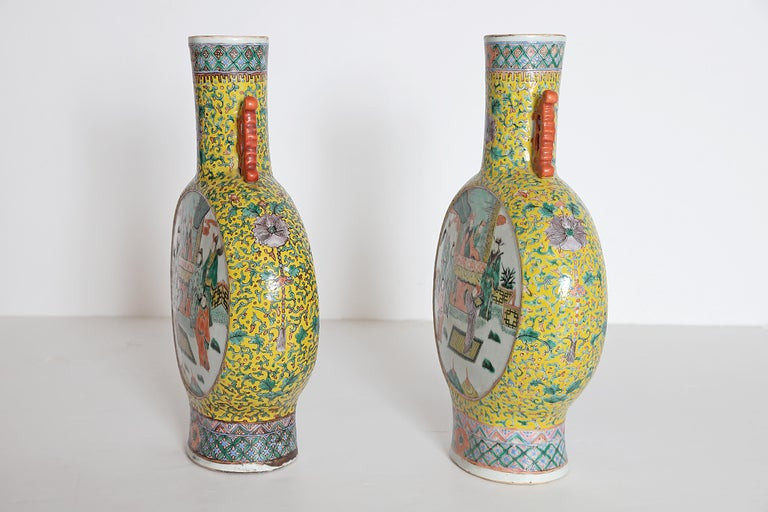 Two (2) Chinese porcelain moon flask vases, a true pair, yellow ground with green and pink flowering vine design with purple flowers, white panels front and back with interior and exterior / landscape scenes, including people and horses (each the