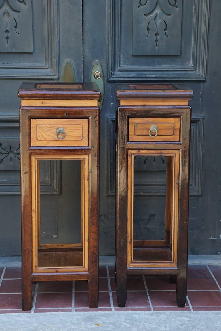 This pair of Chinese provincial elm stands, circa 1890-1900. Probably at one time completely covered in lacquer the wood has been exposed in areas creating an interesting contrast of surfaces. They are made with a single drawer and can be used as