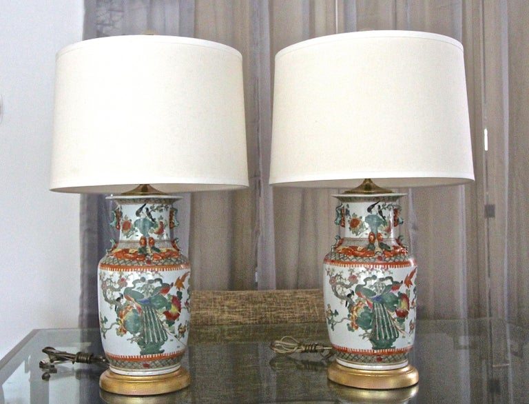 Pair of Chinese Canton porcelain vases in the famille rose palette, now mounted as table lamps on giltwood turned bases. Beautifully crafted including applied relief moulded dragon and kylins, colorfully hand painted with Peacocks, birds, branches,