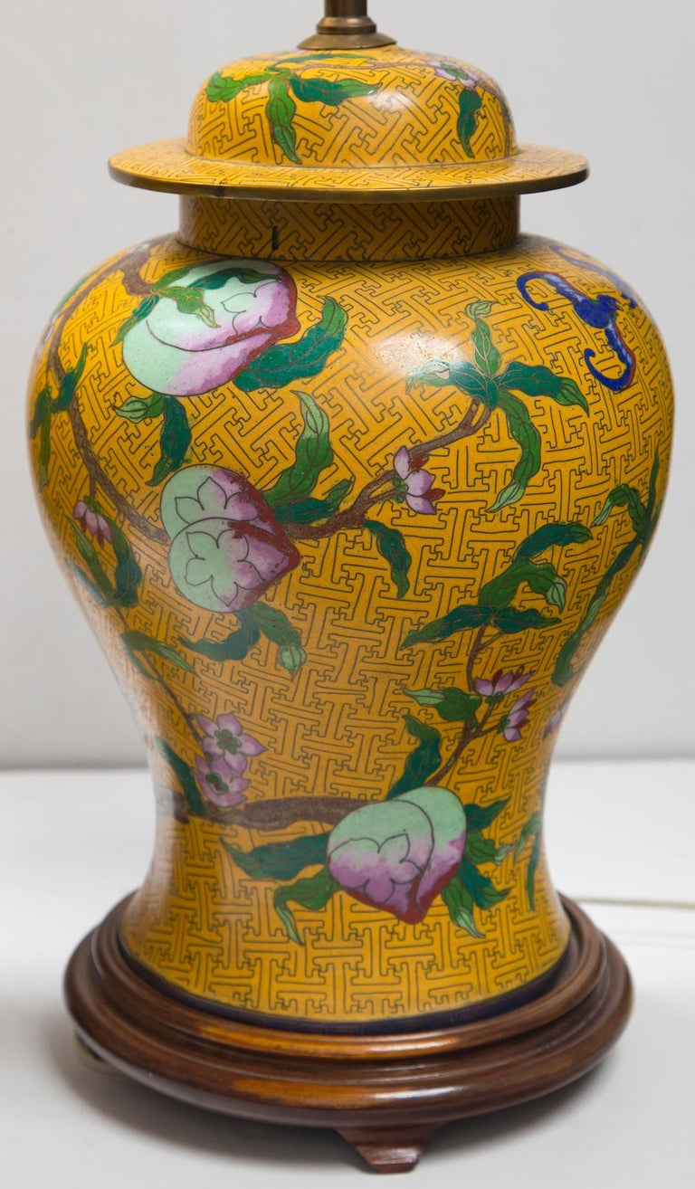 Decorated with bats and peach tree limbs, leaves and peaches. Peaches being a Chinese symbol of longevity. Raised on a turned wood base. Height listed is to the top of the lid.