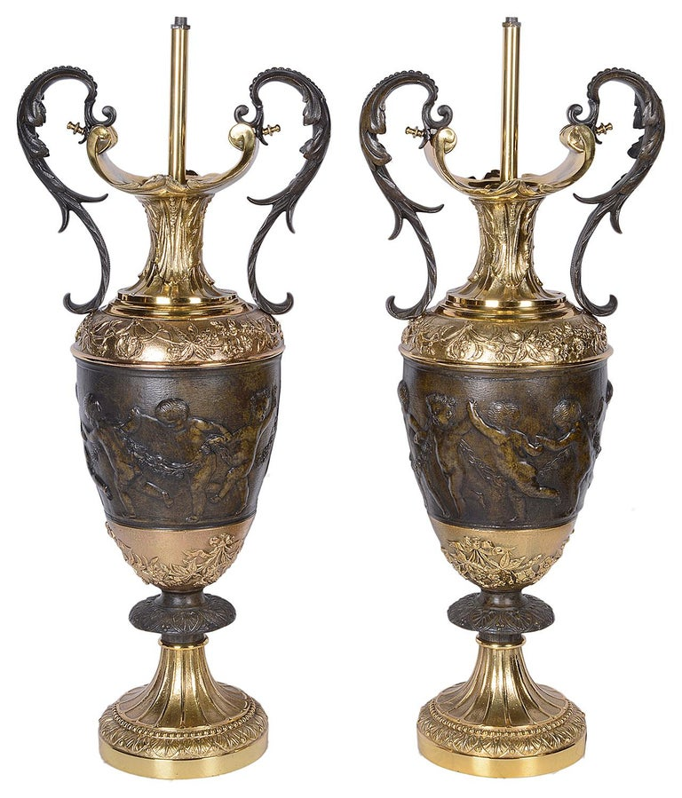 A good quality pair of classical Italian style bronze and gilded ormolu two handle vases / lamps, each having scrolling foliate decoration with dancing cherubs holding hands.