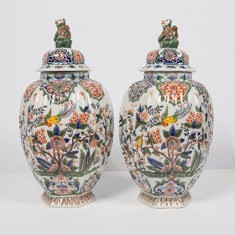 We are pleased to present this lovely pair of Dutch delft polychrome covered jars. They are painted in the cashmere palette of iron red, moss green, and cobalt blue, with accents of bright yellow. The form of the jars is octagonal and the surface is