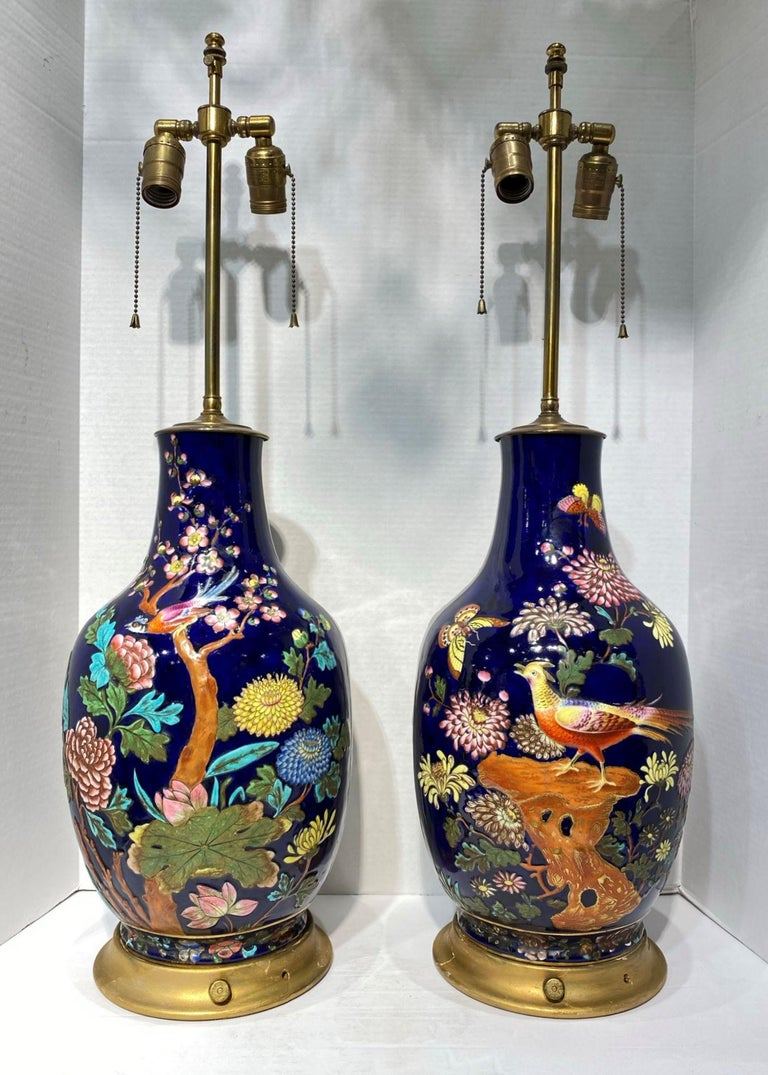 Pair of late 19th century colorful enameled porcelain table Lamps with bird, flowers and butterfly motifs. The decorations are raised and two dimensional. Extremely nice quality painting. The porcelain vases could be French or English.