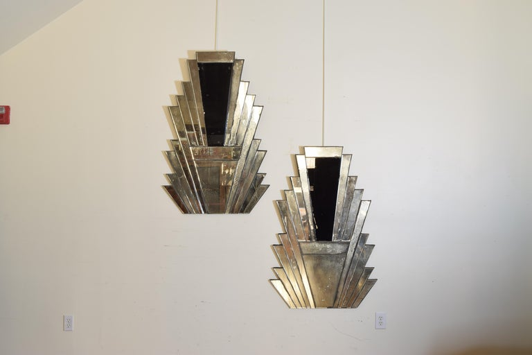 The mirrors constructed of a series of separate layered mirrored pieces stacked and surrounding larger upside down triangular pieces of tempered glass, the backs are covered in black velvet and retain original velvet wrapped hanging wires.