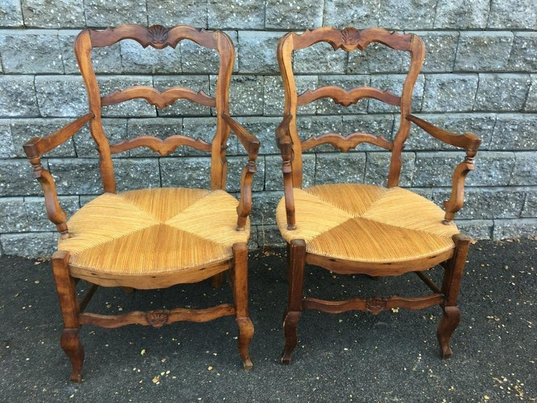 A pair of generously proportioned French country provincial style dining armchairs with carved shell accents on frame and rush seats. Wonderful as head dining chairs or office chairs. Measures: Arm height 26.50 Seat height 15