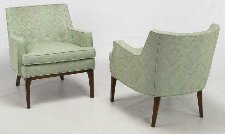 Clean lined pair of Classic club chairs in aquamarine and lavender print silk blend upholstery. Walnut wood legs with sculptural front skirt and radiused corner legs. Loose seat cushion, and button tufted lower back with nice single welt detailing.