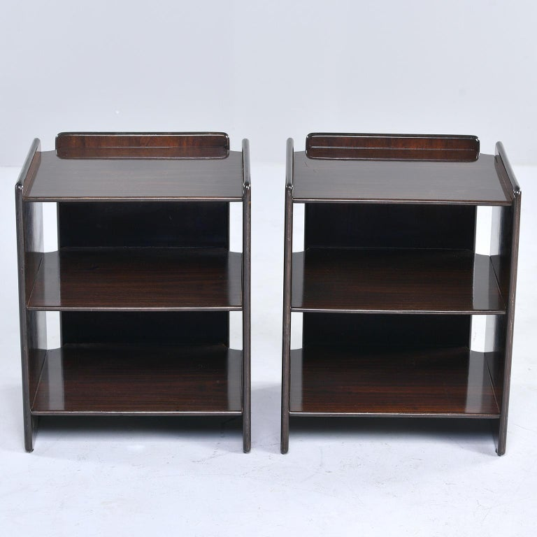 Pair of open shelf style side tables in dark walnut. Modified cubist style with open space between side and back panels. Unknown maker. Found in Italy. Sold and priced as a pair.