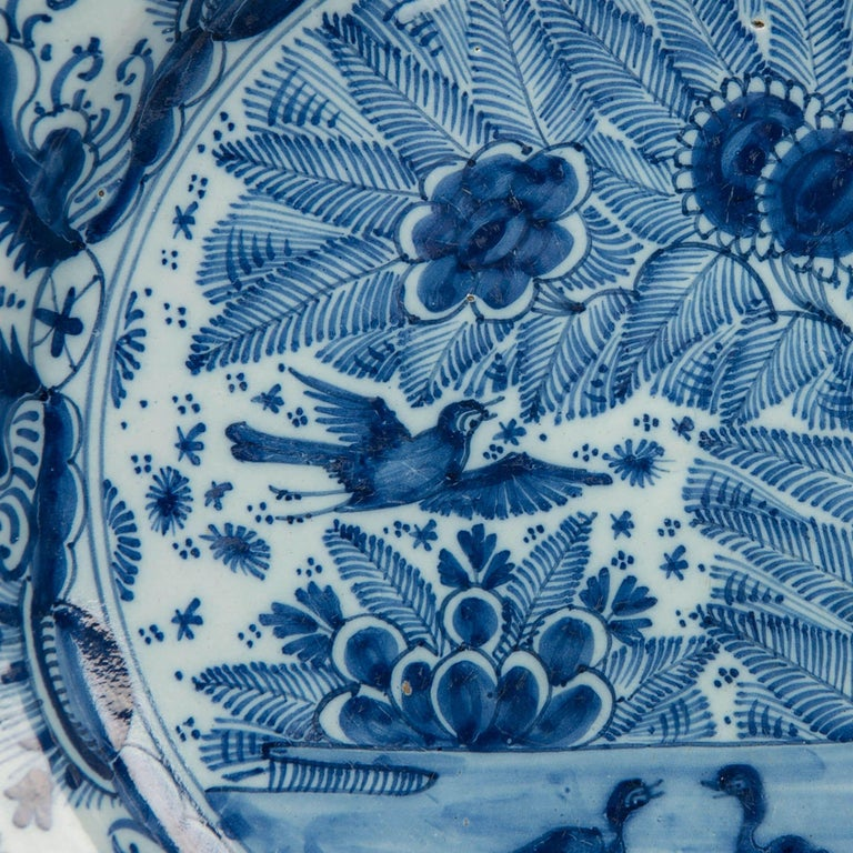 We are pleased to offer this pair of Dutch delft Blue and White chargers showing ducks on a pond and a songbird in flight placed against a naturalistic setting of ferns and sunflowers. The ducks are adorable and seem to be talking to each other