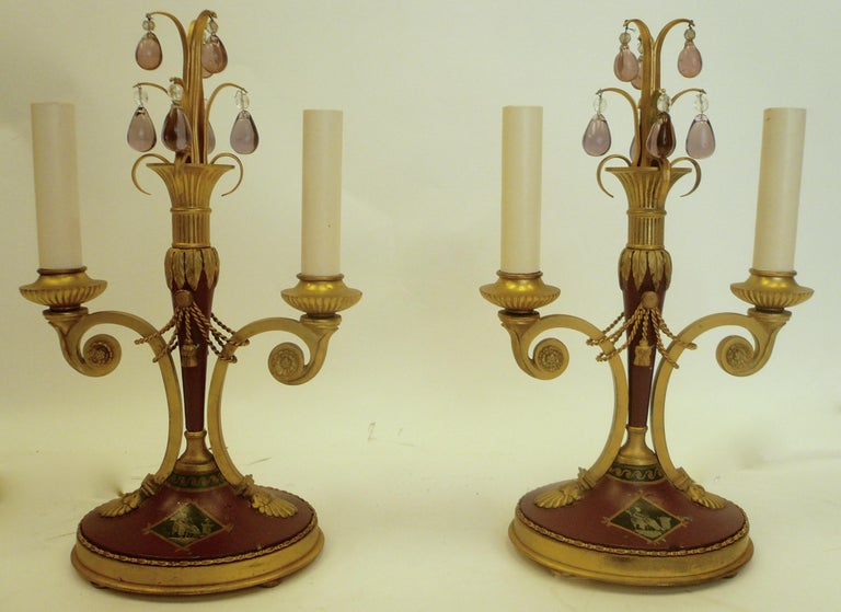 This handsome pair of lamps feature Classical motifs including swags, tassels, and acanthus leaves. The gilt bronze is accented by Wedgwood jasperware style hand painted designs, and trimmed with pale amethyst crystal drops.