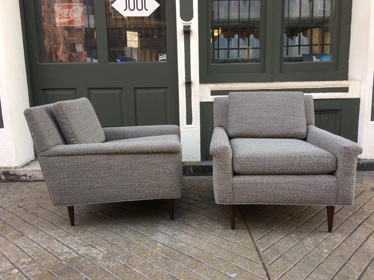 Pair of DUX upholstered lounge chairs, newly upholstered in a nubby gray and white fabric. Walnut legs sit slightly back from corners. Low profile perfect not to block the view!