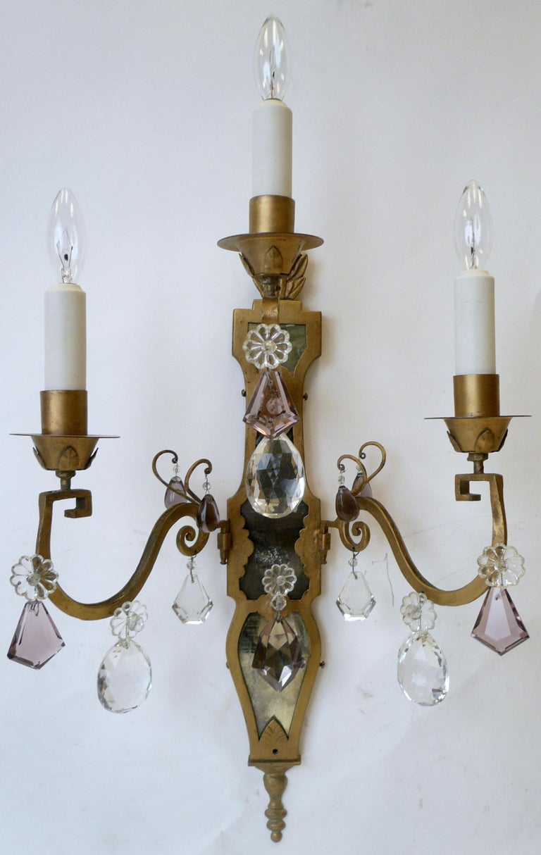 This handmade pair of three-light Continental style sconces feature antique mirrored backs, and gilt flame form finials.