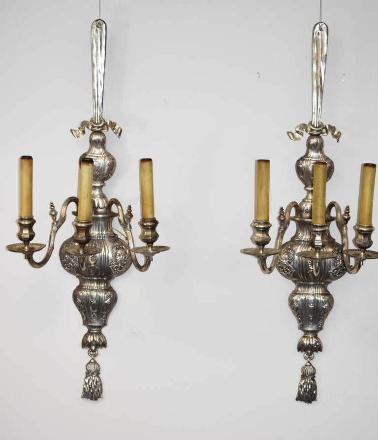 Large pair of silvered three arm sconces by E. F. Caldwell. The sconces retain their original finish and have been recently rewired. The firm was one of the premier designers of electric fixtures and was founded in 1895 and continued in business