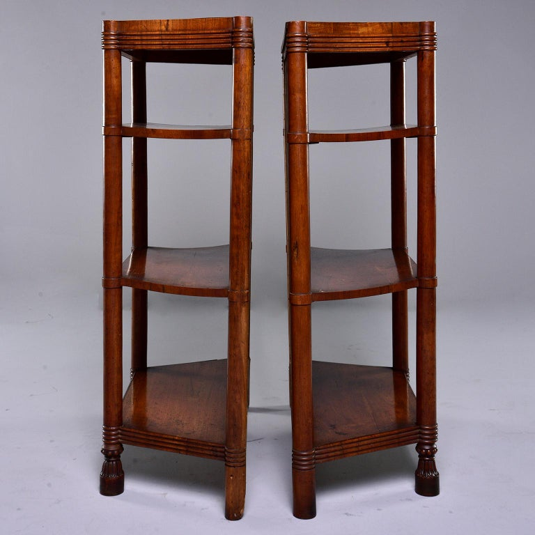 Pair of Italian freestanding shelf units made of wood with walnut veneer, circa 1920s. Shelves feature solid backs, decorative ridging on top and base, footed front legs and three shelves each with angled sides. Unknown maker. Sold and priced as a