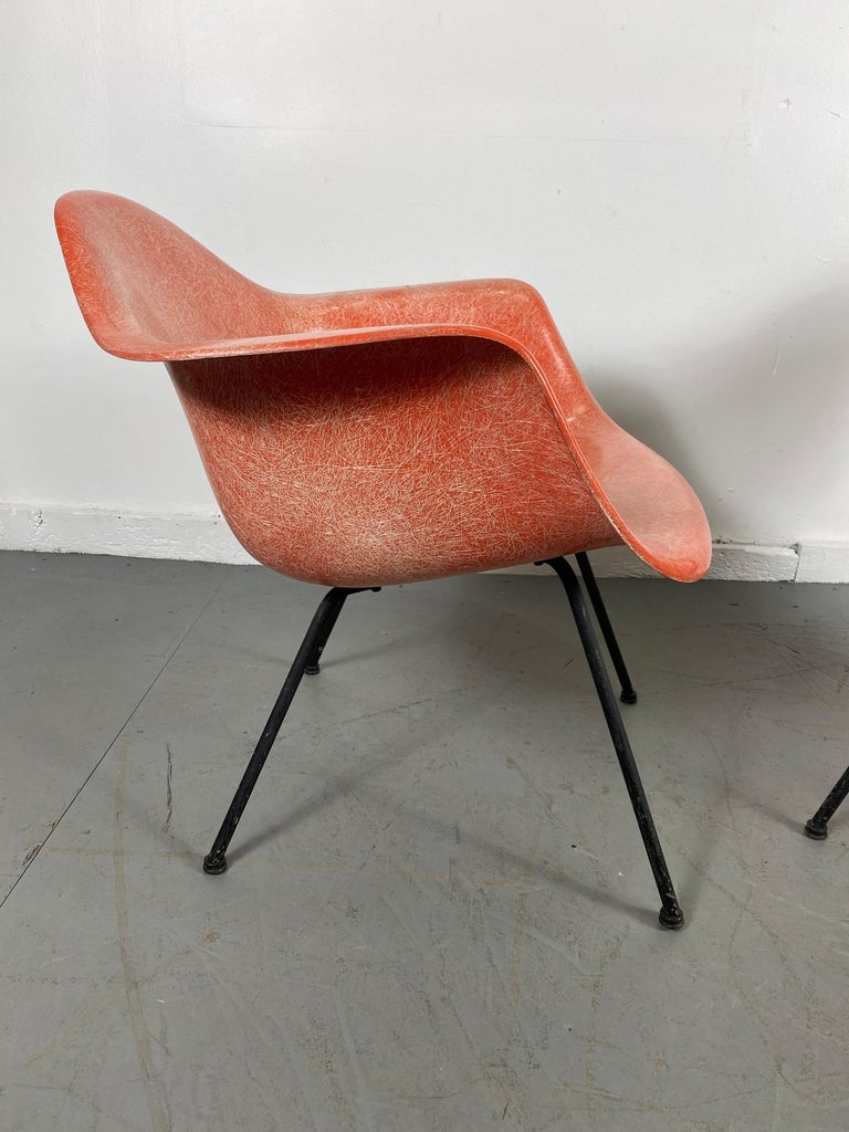 Charles and Ray Eames designed low lounge armshell with X-base. Zinc base, painted black, original screws, original boot glides. Early transitional salmon fiberglass shell 2nd generation mounts, stunning color, finish, exposed fibers.