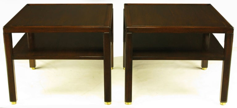Pair of Edward Wormley for Dunbar Classic design two-tier end tables. Solid mahogany legs with raised panel and unexpected recessed brass disc feet. Solid mahogany top border with mahogany raised plateau top.