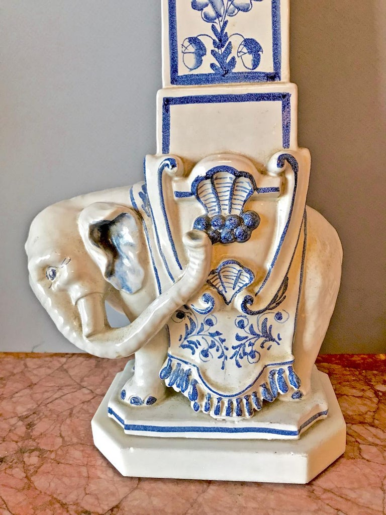 This is a stunning pair of large Italian ceramic lamps inspired by the obelisk found in the Piazza di Minerva, Rome. The midcentury blue and white pottery features a well-sculptured Indian elephant supporting a tall obelisk with neoclassical style