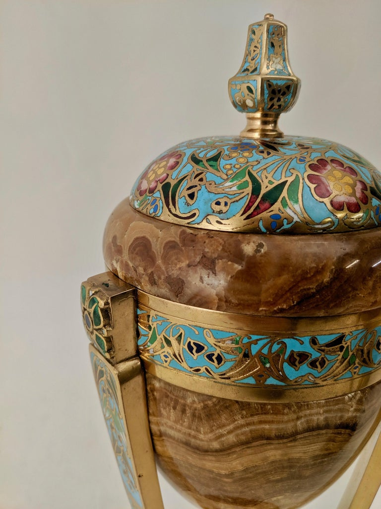 Pair of French Art Nouveau tripod form urns, circa 1890. The brown onyx body and stepped base are richly decorated with floral polychrome champlevé enamel bands. The body of the urn supported by a gilt bronze stem and three horizontal supports, also