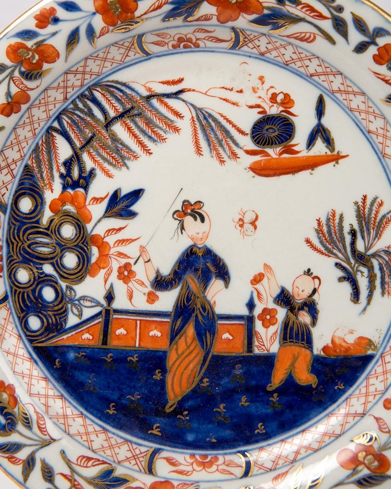A pair of English dishes inspired by Imari decoration showing a scene painted in cobalt blue, orange and gold. We see a lady walking in a garden with her young son. The branches of a prunus tree appear on her left. A butterfly catches the attention