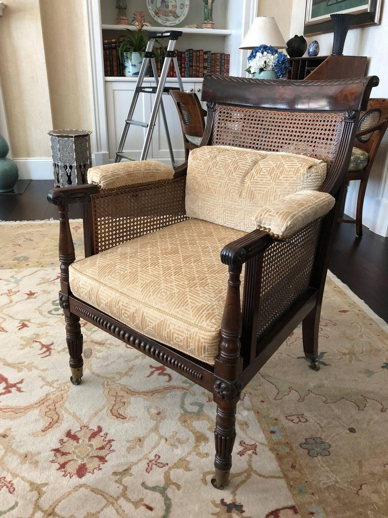 This is a pair of Regency caned library armchairs bergere (off pair--not exactly alike) mahogany with broad back rails caned inset to back, sides and seat having padded arm rests, front legs carved and turned all legs on brass casters purchased in