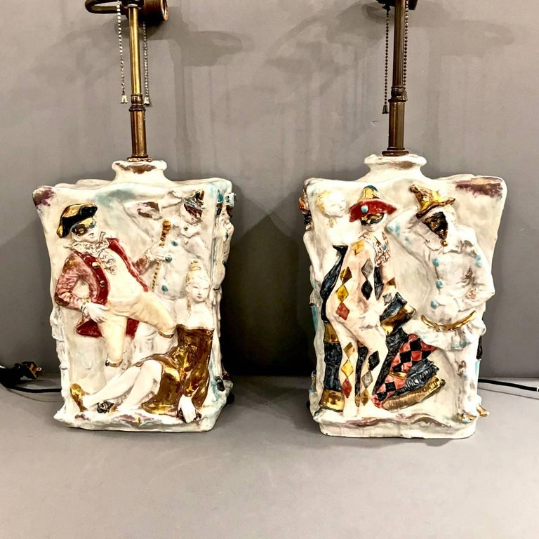 This is a superb set of midcentury Italian ceramic lamps by the renown Prof. Eugenio Pattarino that date to the mid-20th century. The lamps feature high relief Carnival Reveller figures in festive glazed colors. Eugenia Pattarino (1885-1971) was a