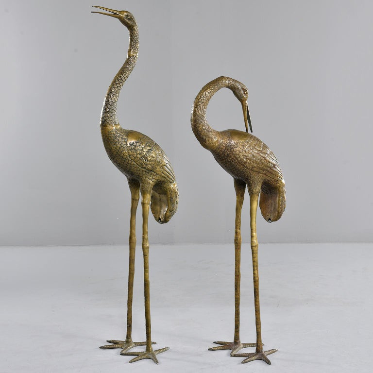 "Extra large pair of cast brass crane sculptures, circa 1960s. Unknown maker. Sold and priced as a pair. Measurements shown are for the taller crane. Smaller crane measures: 47"" high x 17"" wide x 16.5"" deep."