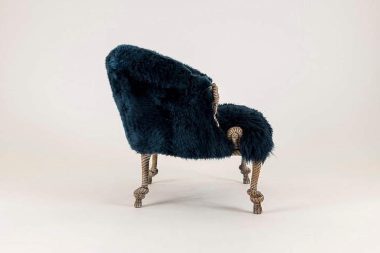 A wildly chic pair of vintage Fournier style gilt carved rope bergère newly upholstered in a navy sheepskin fur. The carving of rope knots are excellent examples of these Napoleon III style chairs.   Overall dimensions of chair including  The