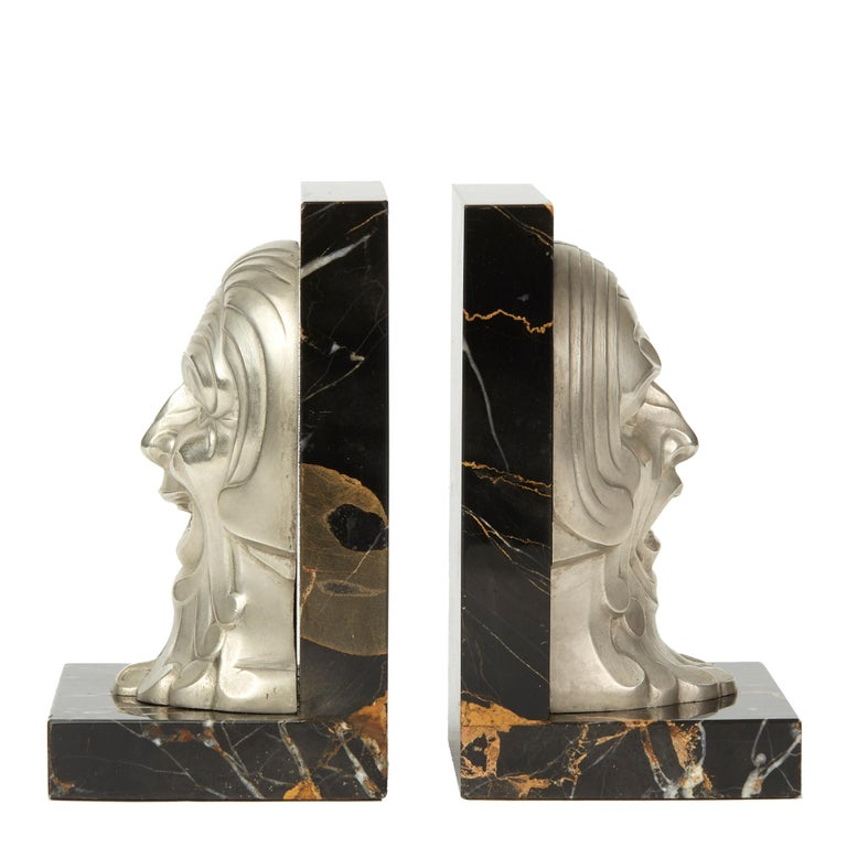 A very stylish pair of French Art Deco marble mounted bookends with moulded polished alloy masks, one depicting comedy and the other tragedy. The masks are mounted on an L shaped black marble stand with orange and white veining and are not marked.