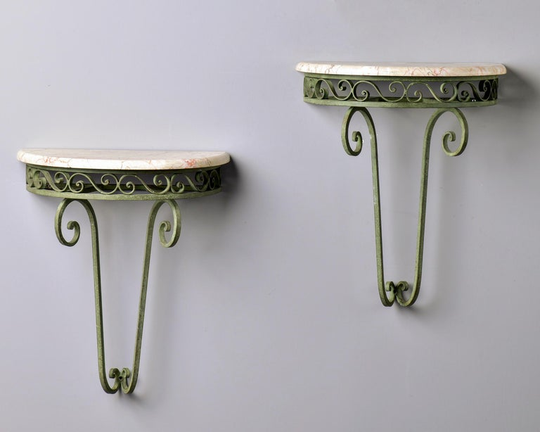 Circa 1930s pair of French wall-hung demilune consoles with iron frames in original green finish and marble tops in shades of cream and white with dark gray and apricot streaks. Unknown maker. Sold and priced as a pair. Unknown maker. Sold and