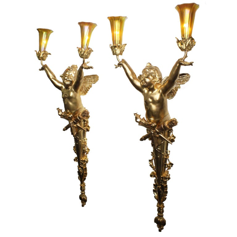 A fine pair of French Belle Époque finely chased figural gilt-bronze two-light wall-lights, by Gustave Joseph Chéret (French, 1838-1894) signed: Joseph Chéret, 25 and Stamped: Soleau-Paris. The Art-Nouveau sconces, each depicting a figure of an open