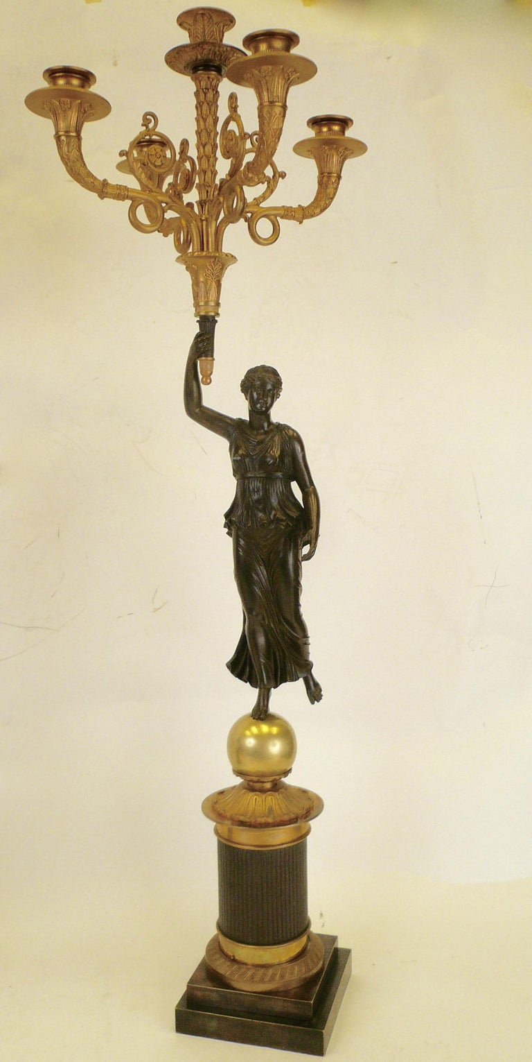 These signed French Empire figural bronze candelabra are by the esteemed maker Claude Francois Rabiat, 1756-1815. The figures represent Nike the goddess of victory, and the casting is extremely detailed and beautifully finished in patinated bronze.