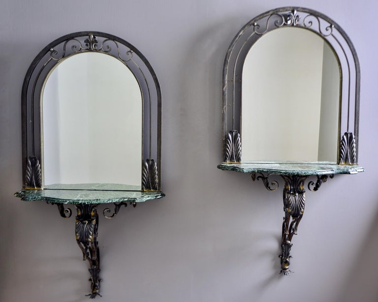 Circa 1930s pair of French wall consoles with iron-framed mirrors. Wall mounted arched iron frames feature open work and metal tole details, green marble table tops and decorative iron supports. Sold and priced as a pair. Unknown maker.