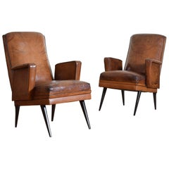 Pair of French Late Art Deco Leather Upholstered and Ebonized Wood Bergeres