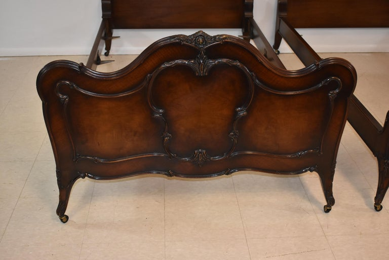Pair of French Louie XV style walnut twin bed frames by Irwin Furniture. Figured walnut panels with applied carvings.