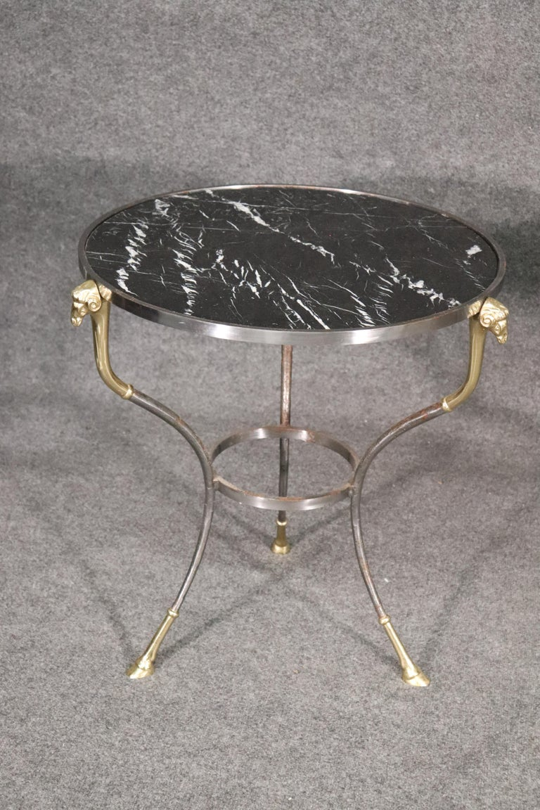These are beautifully made brass and steel geuridons. The tables feature the classic rams head terminals and cloven hooved feet done in brass. The marble tops are black with white veins. These beautiful tables may be just what you're looking for.