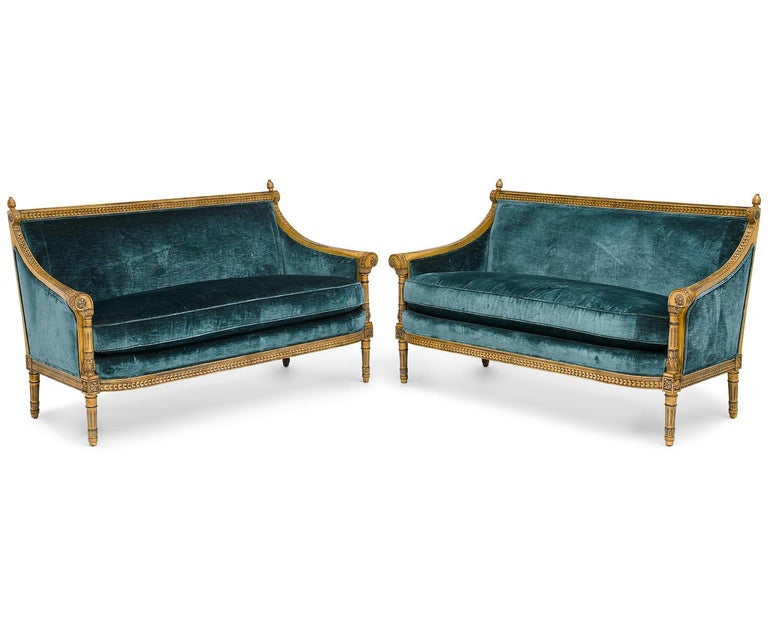 A pair of Louis XVI style carved and Laqué gilded bergère settees. The elegant pair of carved loveseats, upholstered in a blue velvet, with padded backs and sides and a cushion seat, the swagged armrests decorated with floral rosettes and topped