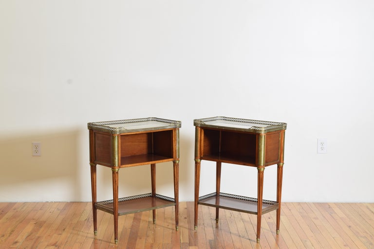 Each rectangular shaped commode having a shaped white marble top surrounded by a 3/4 pierced brass gallery resting atop conforming cases with open fronts and brass mounted corners, raised on brass mounted circular tapering reeded legs joined by a