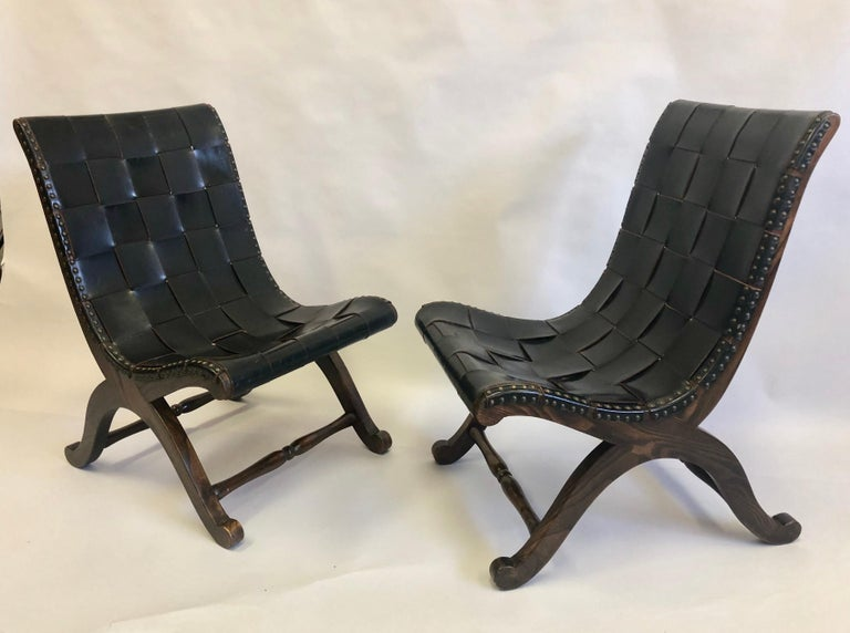 Pair of French Mid-Century Modern neoclassical black leather strap lounge or slipper chairs attributed to Pierre Lottier. The wood frames are arranged in a classical curile X-form and the black leather straps are interlaced and studded to the