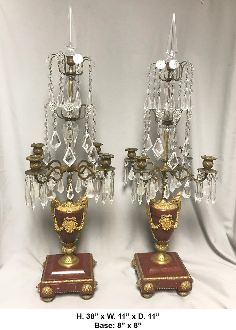 Extremely fine pair of 19th century French Louis XVI style ormolu mounted rouge marble four-light girandole lamps.  The beautiful girandoles are surmounted by a cut crystal spike, above two tiers of cut crystal prisms and adorned with Rock Crystal