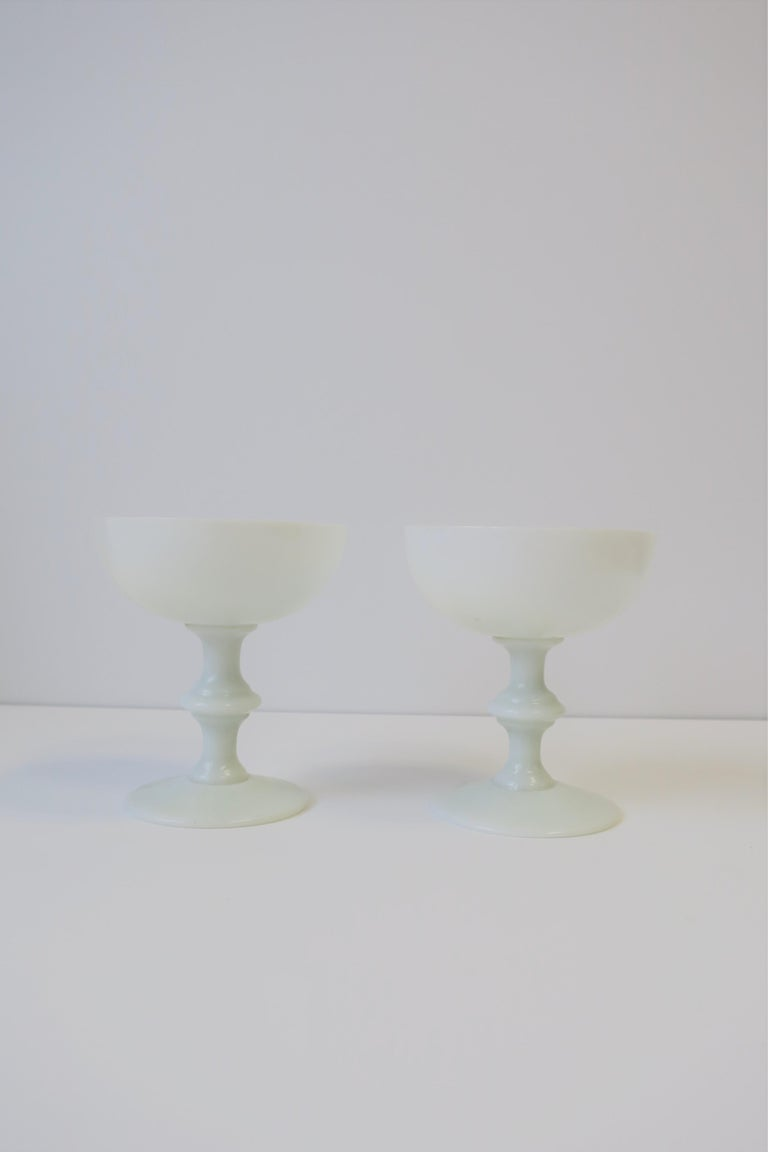 A beautiful pair of French white opaline Champagne glasses by Portieux Vallerysthal, circa early 20th century, France.   Each glass measures: 4.75